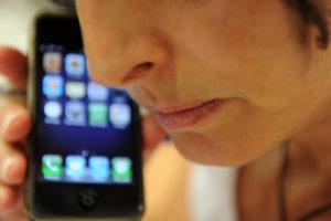 Una donna parla a uno smartphone a Pisa, 23 giugno. ANSA / FRANCO SILVI