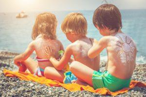 Little boys and girl applying sun protection lotion on the beach